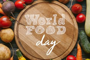 "Variety of colorful vegetables by cutting board with ""world food day"" lettering"
